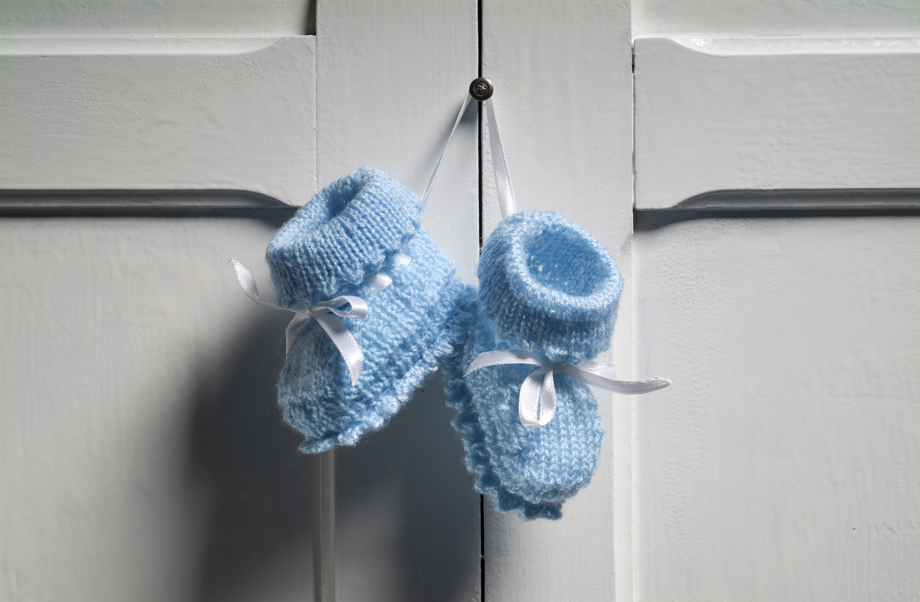 blue baby booties hang on wall